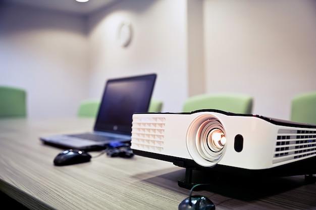 Projektor i laptop na stole.