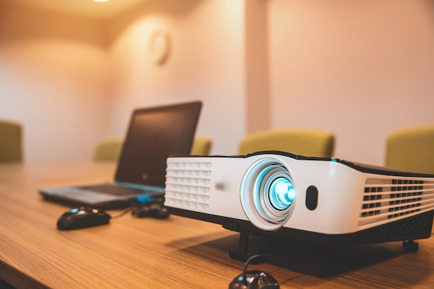 Projektory i komputery zainstalowane na stołach w sali konferencyjnej.