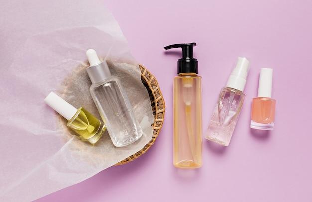 Projektowanie opakowań kosmetyków organicznych. płaska, leżąca, widok z góry butelka z pompką z przezroczystego szkła, słoik na pędzle, słoik z serum nawilżającym w papierowym koszu na fioletowym tle. kosmetyki naturalne spa