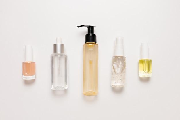 Projektowanie opakowań kosmetyków organicznych. płaska świecąca, widok z góry przezroczysta szklana butelka z pompką, słoik na pędzle, słoik na serum nawilżające na białym tle. kosmetyki naturalne spa