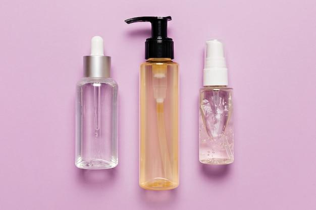 Projektowanie opakowań kosmetyków organicznych. płaska, ułożona, widok z góry przezroczysta szklana butelka z pompką, słoik na pędzle, słoik z serum nawilżającym na fioletowym tle. kosmetyki naturalne spa