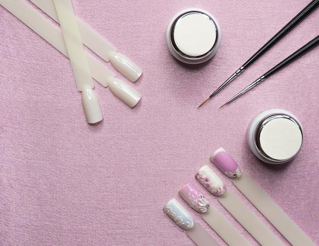 Projektowanie paznokci. farby, pędzle i typy na różowym tle.