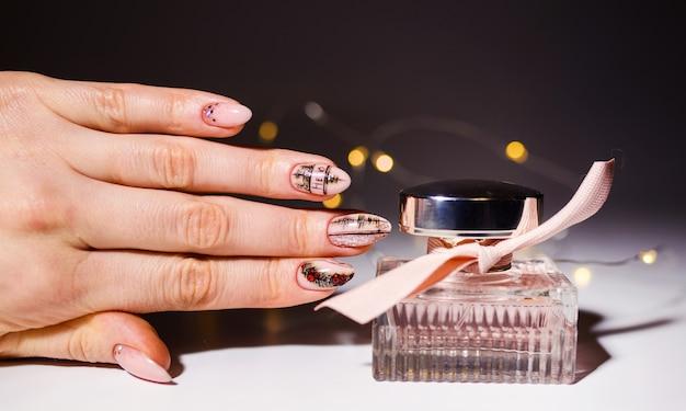 Projektowanie paznokci. ręce z jasnym różowym i zielonym manicure