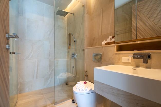 Projektowanie wnętrz willi, domu, domu, mieszkania i apartamentu obejmuje umywalkę, lustro, toaletę i prysznic z widokiem w nowoczesnej łazience