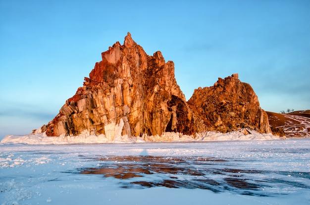 Promień słońca nad skałą shamanka w pobliżu khuzhir późną zimą w wieczór zachód słońca.