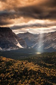 Promień słońca świecący na skaliste góry w jesiennym lesie w parku narodowym banff, kanada