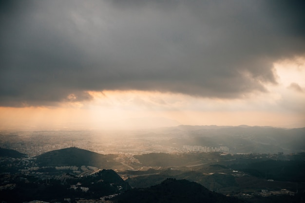 Promień światła przenikający przez ciemne niebo nad górą pejzażu
