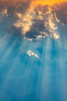 Promień światła słonecznego przedzierający się przez chmury o zachodzie słońca.