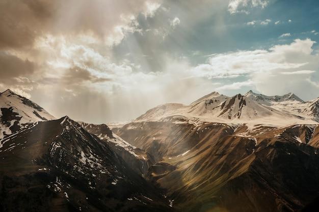 Promienie słońca przedostają się przez chmury do zaśnieżonego wysokiego pasma górskiego