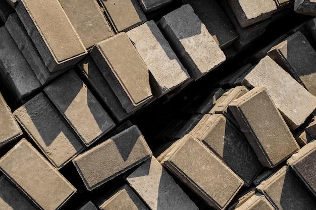 Promienie słoneczne na betonowych płytach chodnikowych. tło kostek, leżących w arbitralnym porządku