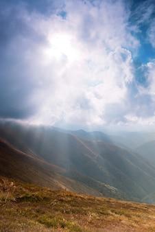 Promienie słoneczne przez chmury na niebie w paśmie górskim