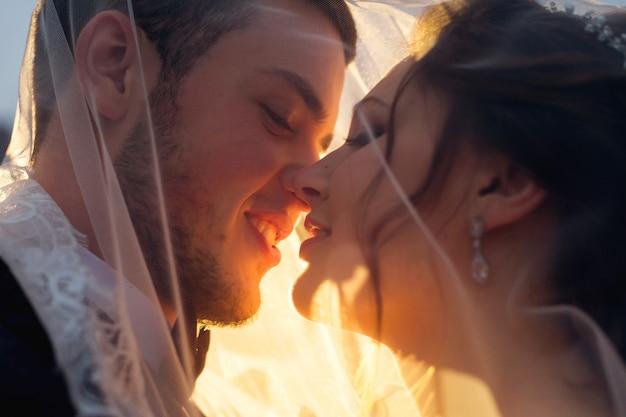 Promienie słoneczne świecą na nowożeńców, którzy chcą całować się pod zasłoną ślubną