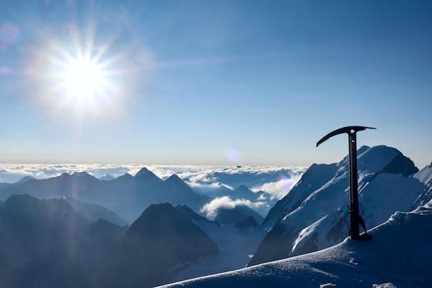 Promienie słoneczne z toporem lodowym lub narzędziem i pasmem górskim