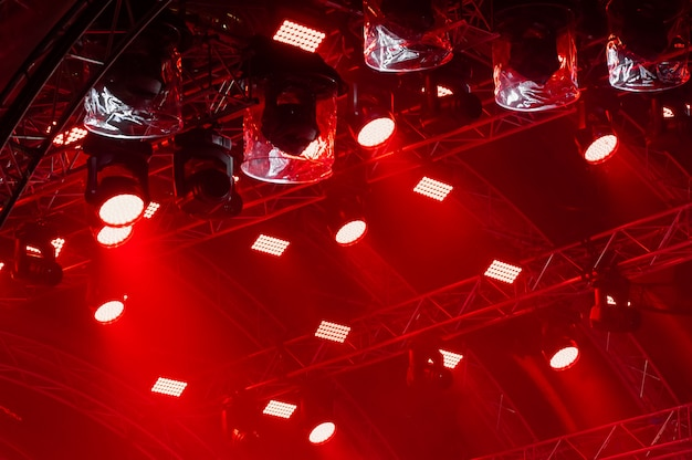 Promienie światła z koncertowego oświetlenia na ciemnym tle nad ekranem projektora.