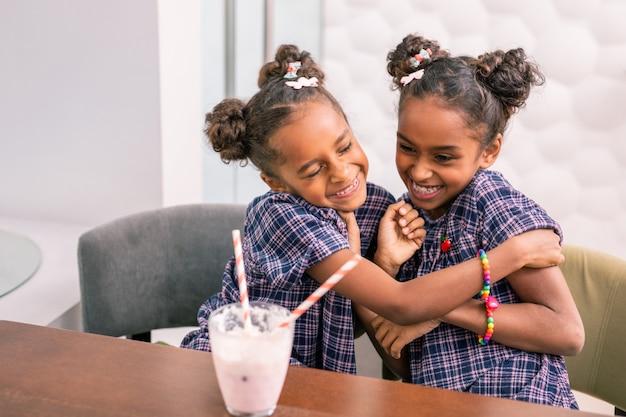 Promieniejące rodzeństwo. dwoje uroczego, rozpromienionego rodzeństwa czuje się niezwykle zabawnie przytulając się i głośno śmiejąc