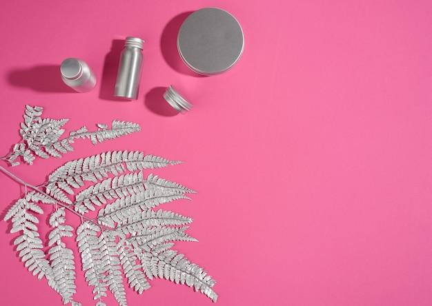 Promieniste metalowe słoje, butelka i srebrzysta gałązka rośliny na różowym tle. opakowania na krem, żel, serum, reklamę i promocję produktu. makieta