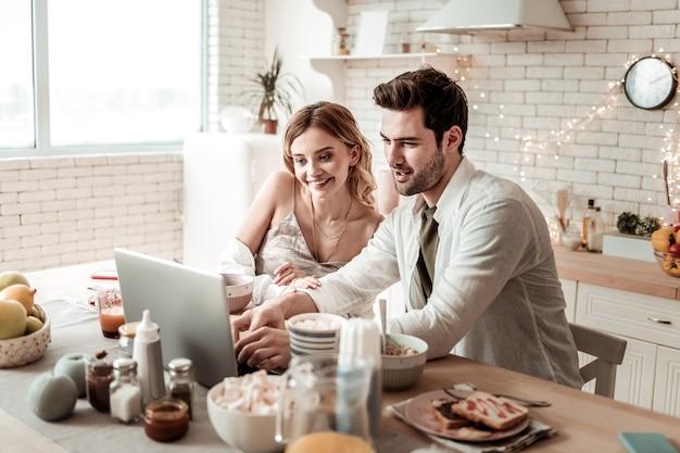 Promienna dama. długowłosa, rozpromieniona ładna kobieta w domowych ubraniach wyglądająca na szczęśliwą spędzającą czas z mężem