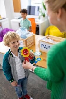 Promienny chłopiec. słodki, rozpromieniony chłopiec czuje się szczęśliwy podczas odbierania nagrody w szkole po sortowaniu odpadów