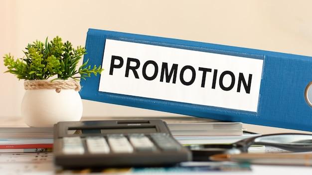 Promocja - niebieski segregator na biurku w biurze z kalkulatorem, długopisem i zieloną rośliną doniczkową. może być używany do koncepcji biznesowej, finansowej, edukacyjnej, audytowej i podatkowej. selektywne skupienie.