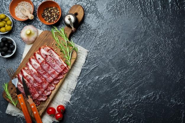 Prosciutto crudo lub jamon. surowa szynka na czarno.