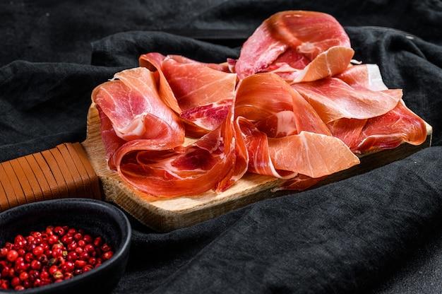 Prosciutto crudo, włoskie salami, szynka parmeńska. talerz antipasto. czarne tło, widok z góry.