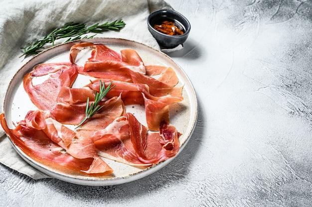 Prosciutto crudo, włoskie salami, szynka parmeńska. talerz antipasto. szare tło, widok z góry, miejsca na tekst