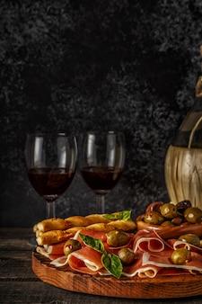 Prosciutto, krakersy, paluszki chlebowe z czerwonym winem.