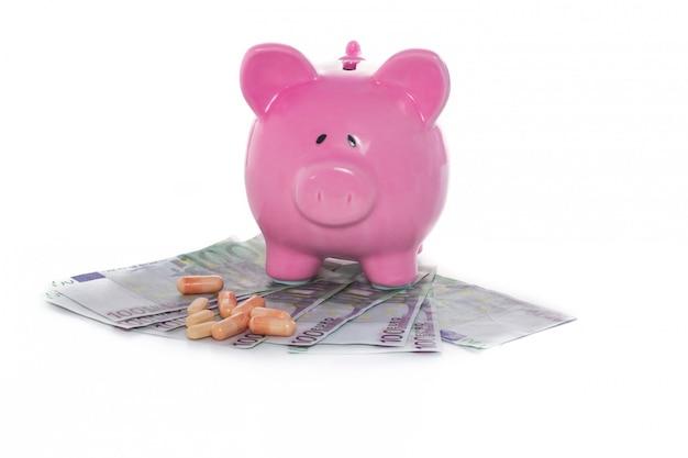 Prosiątko bank na stosie dolary z pastylkami