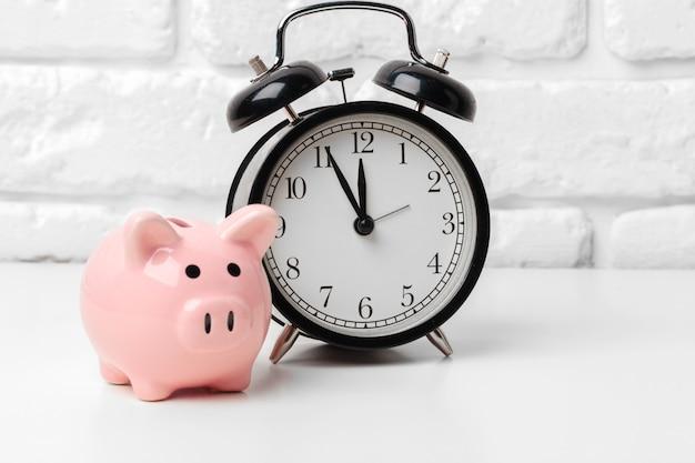 Prosiątko bank save monetę, budzika, czasu i pieniądze pojęcie.
