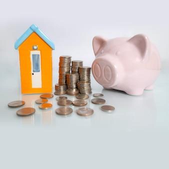 Prosiątko bank z małym domem i monetą na białym tle