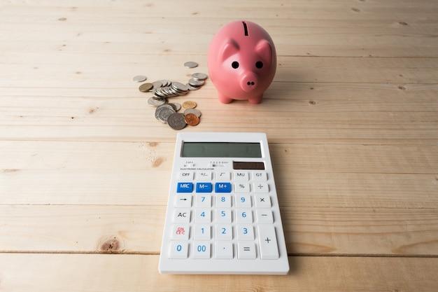 Prosiątko bank z monetami i kalkulatorem