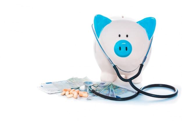 Prosiątko banka obsiadanie na stosie dolary z stetoskopem i pigułkami