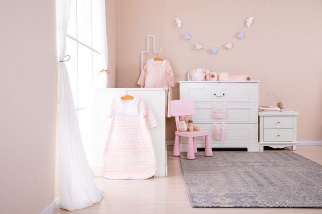 Prosta, biała sypialnia dla dziecka z łóżeczkiem i dywanikiem