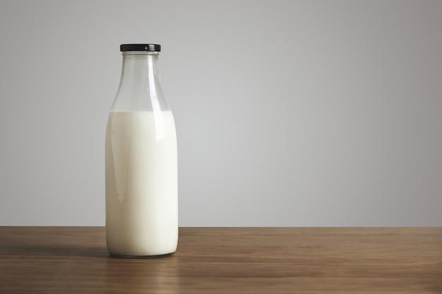 Prosta butelka w stylu vintage wypełniona świeżym mlekiem na grubym drewnianym stole. zamknięty czarną skuwką. kawiarnia