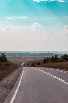 Prosta droga z oznakowaniem na tle przyrody. otwarta droga w przyszłości, bez samochodów, auto na drodze asfaltowej przez zielony las, drzewa. chmury na błękitnym niebie latem, słońce, słoneczny dzień. widok z dołu