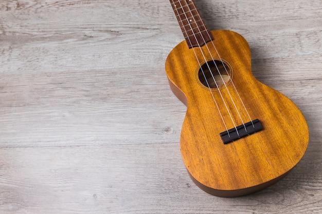 Prosta klasyczna drewniana muzykalna gitara na drewnianym tle