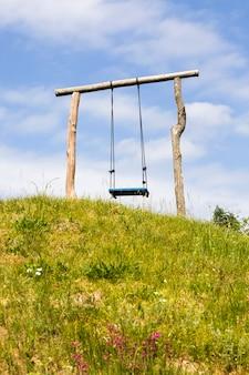 Prosta prymitywna drewniana huśtawka ustawiona na wzgórzu, w okresie letnim, miejsce do wypoczynku na małej, wiejskiej okolicy