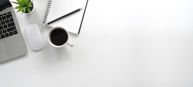 Prosta przestrzeń do pracy - kreatywne, płaskie biurko. odgórnego widoku stół z laptopem, notatnikami i filiżanką na białym tle. panorama transparent tło z miejsca kopiowania.