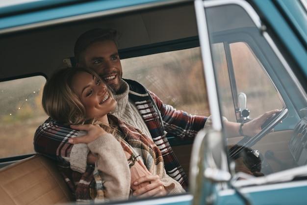 Prosta radość kochania. piękna młoda para obejmując i uśmiechając się siedząc w mini vanie w stylu retro