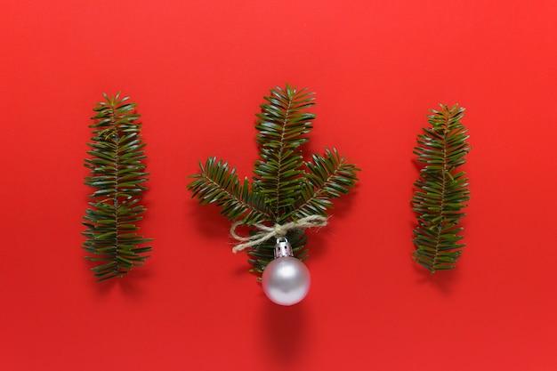 Prosta świąteczna nawierzchnia z trzema gałązkami i jedną różową bombką na czerwonej powierzchni