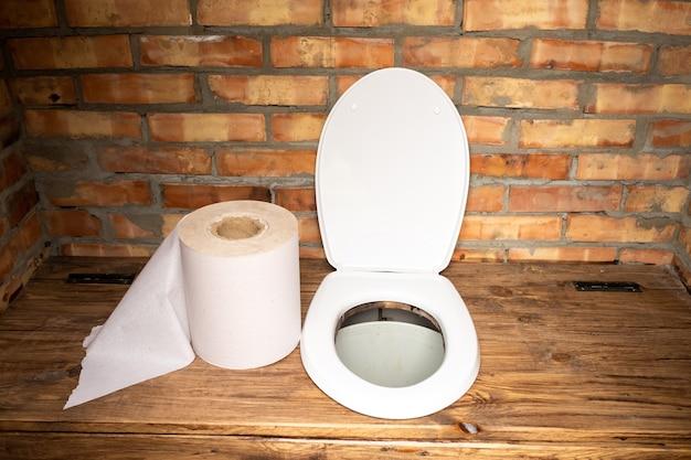 Prosta wiejska toaleta z dużą rolką papieru toaletowego