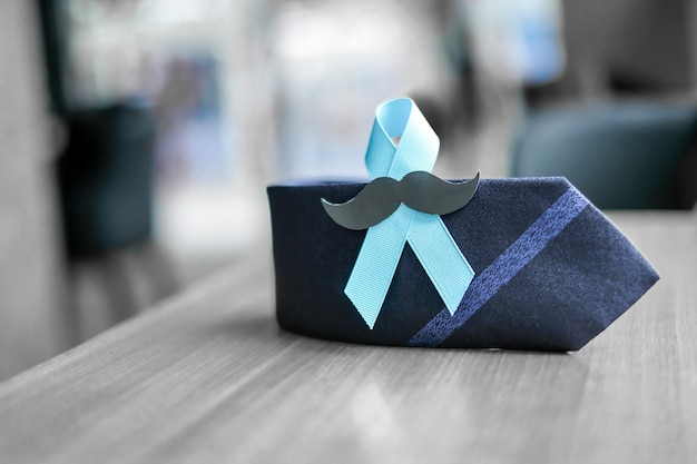 Prostate cancer awareness, light blue ribbon z wąsem i krawatem