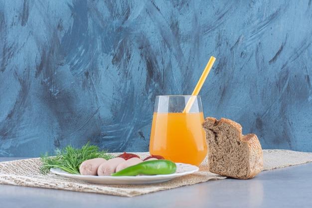 Proste angielskie śniadanie. kiełbasa i sok pomarańczowy z pieczywem.