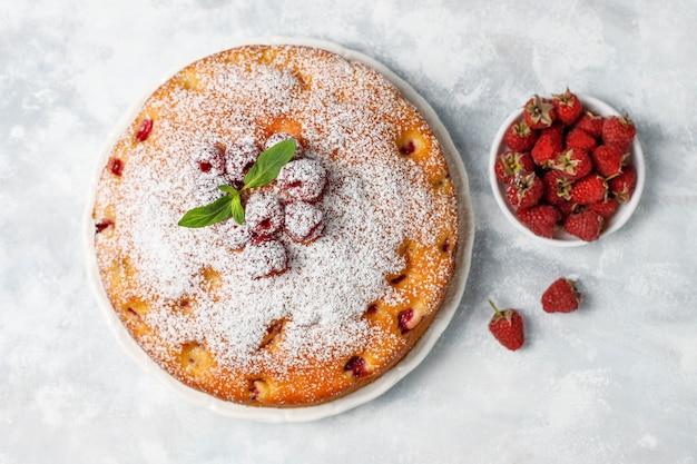Proste ciasto z cukrem pudrem i świeżymi malinami na świetle. letni deser jagodowy.
