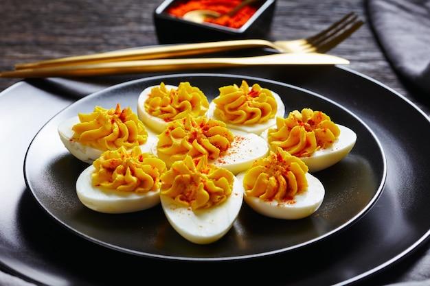 Proste diabelskie jajka z rozbitych żółtek musztarda, majonez, biały ocet posypane wędzoną papryką na czarnym talerzu na ciemnym drewnianym stole, złote sztućce, zbliżenie