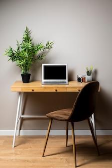 Proste drewniane biurko z krzesłem i laptopem