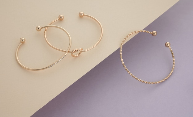 Proste nowoczesne złote bransoletki na delikatnych pastelowych kolorach tle