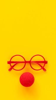Proste plastikowe oprawki okularów w kolorze czerwonym i nos klauna z czerwonej pianki.