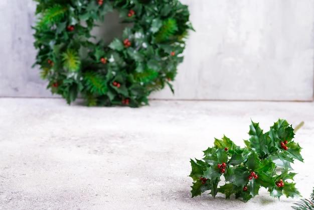 Proste święta bożego narodzenia z ostrokrzewem, liśćmi ostrokrzewu i drobnymi czerwonymi owocami na kamieniu