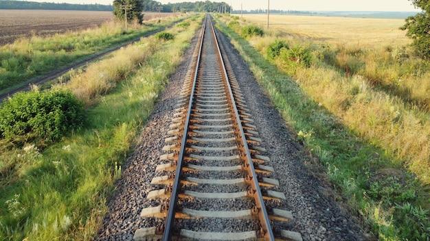 Proste tory kolejowe, droga kolejowa przez pola i lasy.